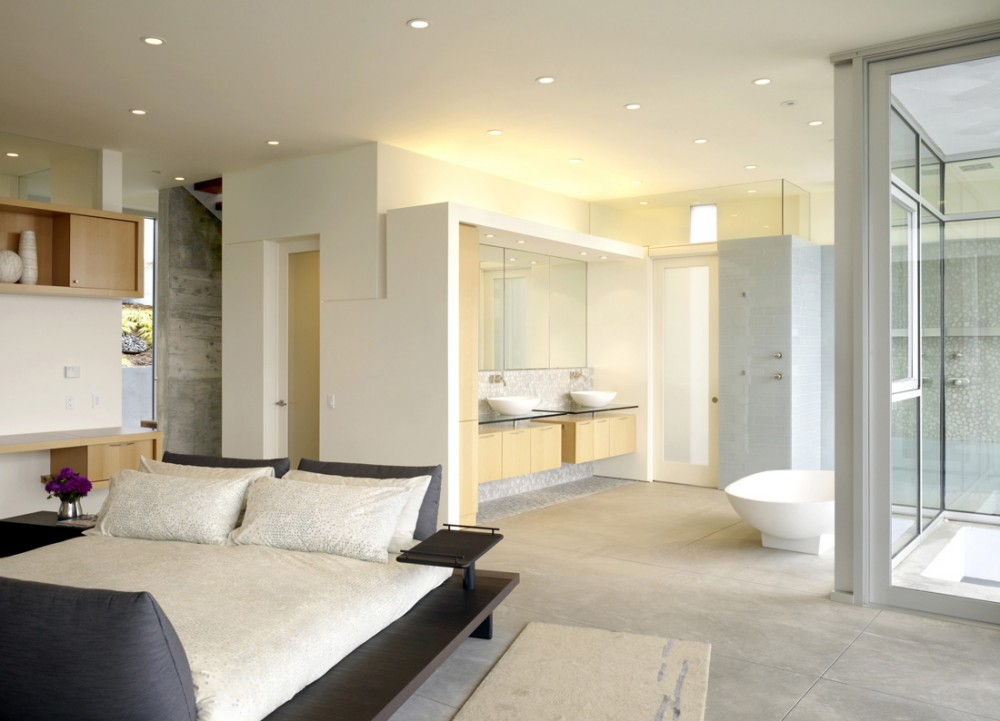 A master bedroom with an open bathroom design